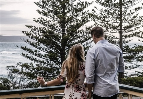 Couple standing on a balcony in Lorne overlooking water
