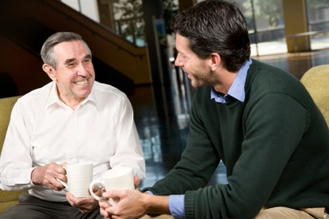 Older man  having coffee with younger man