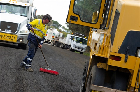 Worker sweeping road with construction vehicles